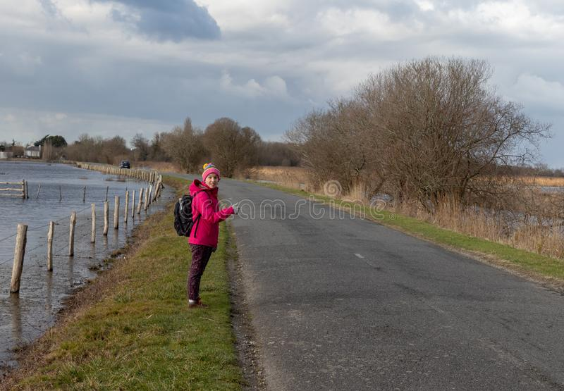 Girl hitchhiking on a rural road wearing a pink coat stock image