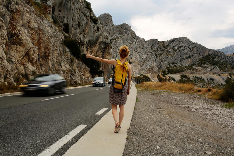 Girl hitchhiking with thumb up. Pretty girl young woman traveler hitchhiking with thumb up hand gesture during summer vacation on mountain road royalty free stock image
