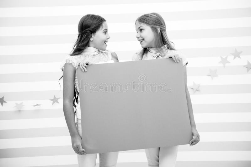 Girl hold announcement banner. Girls kids holding paper banner for announcement. Children happy with blank paper. Announcement copy space. Kids announcement stock images