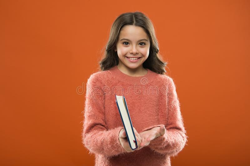 Girl hold book read story over orange background. Child enjoy reading book. Book store concept. Wonderful free childrens. Books available to read. Childrens royalty free stock image