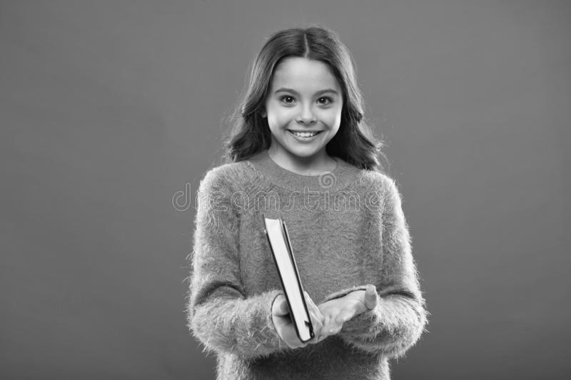 Girl hold book read story over orange background. Child enjoy reading book. Book store concept. Wonderful free childrens. Books available to read. Childrens royalty free stock photography