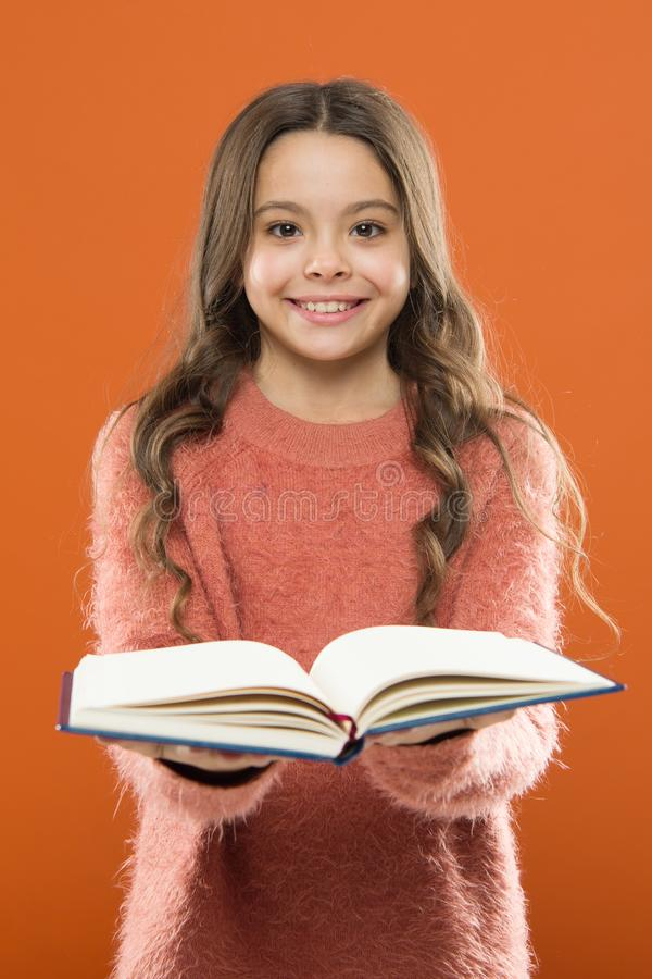 Girl hold book read story over orange background. Child enjoy reading book. Book store concept. Wonderful free childrens. Books available to read. Reading stock images