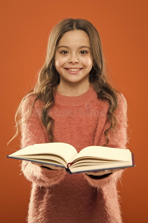 Girl hold book read story over orange background. Child enjoy reading book. Book store concept. Wonderful free childrens. Books available to read. Reading stock photos