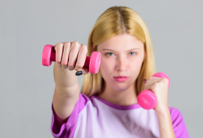 Girl hold dumbbells. Biceps exercises for female. Fitness instructor. Healthy lifestyle concept. Woman fitness coach. Exercising with dumbbells. Easy exercises stock image