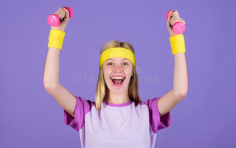 Girl hold dumbbells wear bright wristbands. Vintage sport concept. Woman exercising with dumbbells. Easy exercises with. Dumbbells. Workout with dumbbells royalty free stock photo