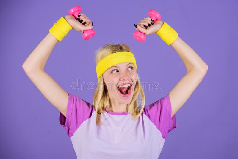 Girl hold dumbbells wear wristbands. Sport and fitness concept. Woman exercising with dumbbells. Easy exercises with. Dumbbells. Workout with dumbbells. Biceps royalty free stock photo