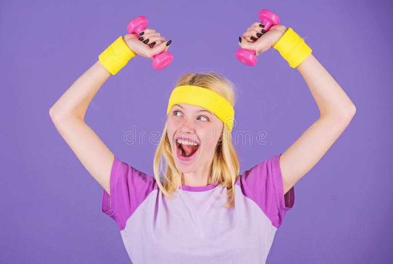 Girl hold dumbbells wear wristbands. Sport and fitness concept. Woman exercising with dumbbells. Easy exercises with. Dumbbells. Workout with dumbbells. Biceps stock photos