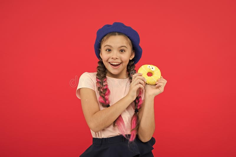 Girl hold glazed cute donut in hand red background. Kid smiling girl ready to eat donut. Sweets shop and bakery concept royalty free stock photo