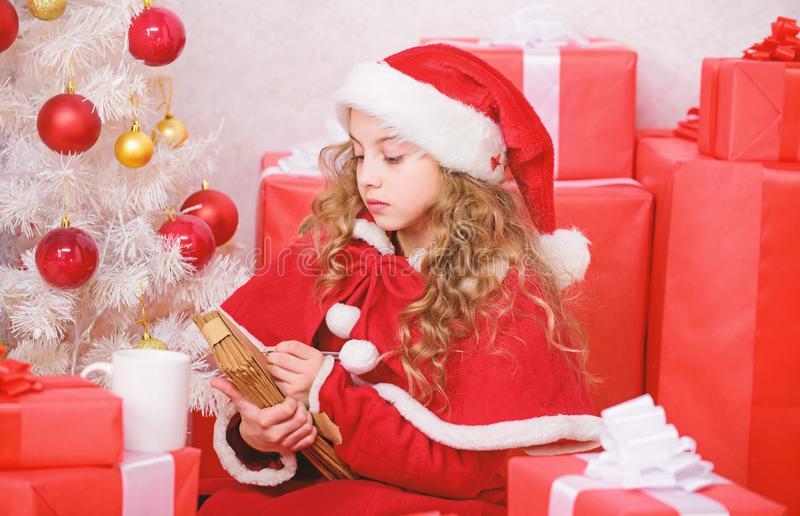 Girl hold pen and paper near christmas tree and gift box. Believe in miracle. Send letter for santa. Wish list. Child. Santa costume enjoy christmas eve. Child stock photo