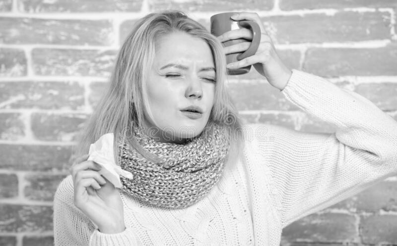 Girl hold tea mug and tissue. Runny nose and other symptoms of cold. Drinking plenty fluid important for ensuring speedy stock photo