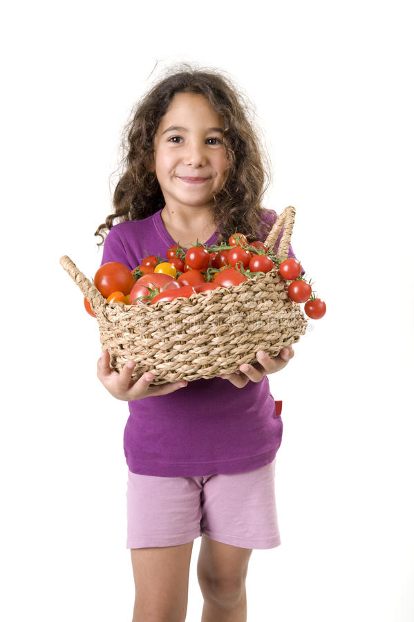 Girl holdin a basket of tomatoes royalty free stock images