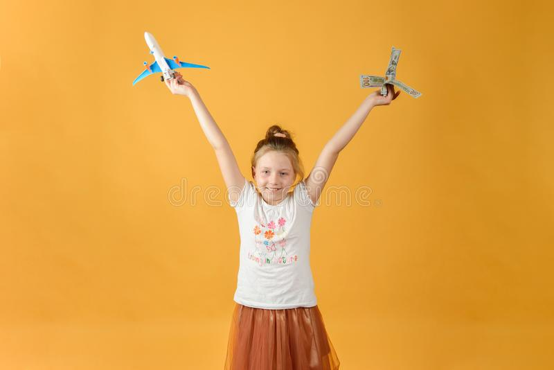 Girl holding airplane and money in her hands, concept of vacation and travel stock image