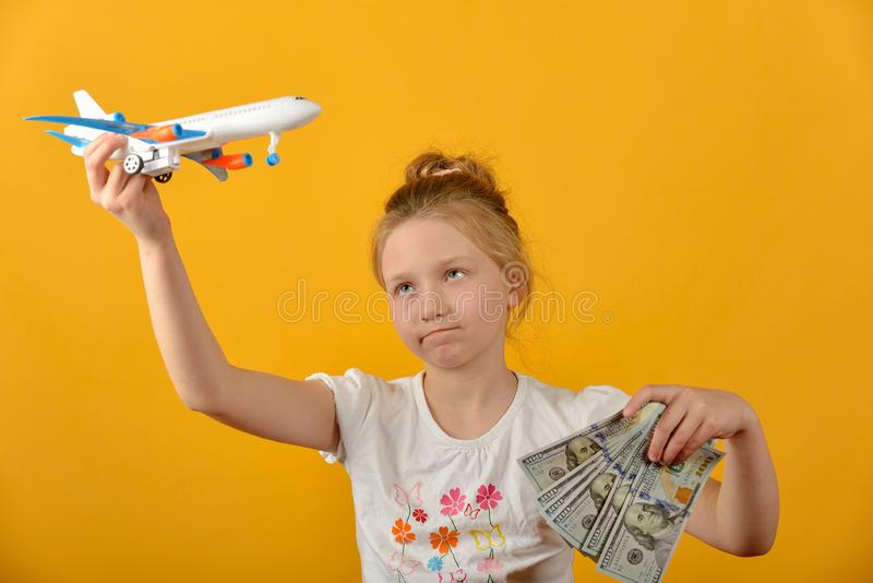 Girl holding airplane and money in her hands, concept of vacation and travel stock photo