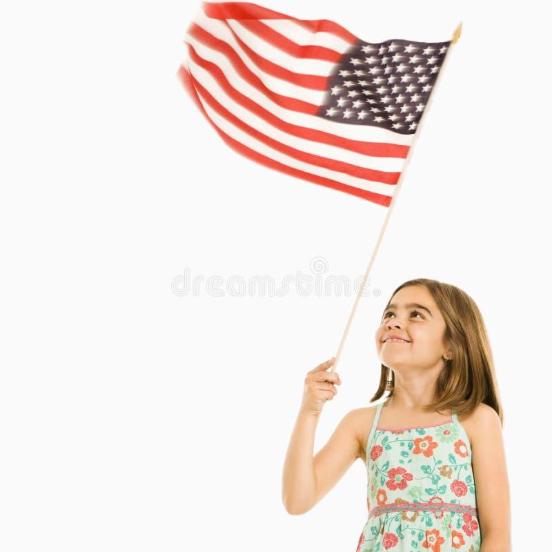 Girl holding American flag. Girl holding American flag against white background royalty free stock images