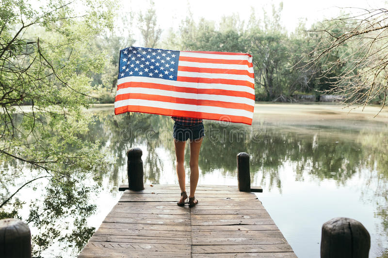 Girl holding an american flag in nature royalty free stock image