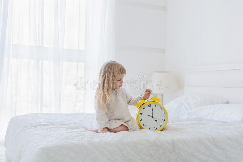 Girl holding analog alarm clock in bedroom. Girl holding analog alarm clock while sitting on the bed in the morning royalty free stock photos
