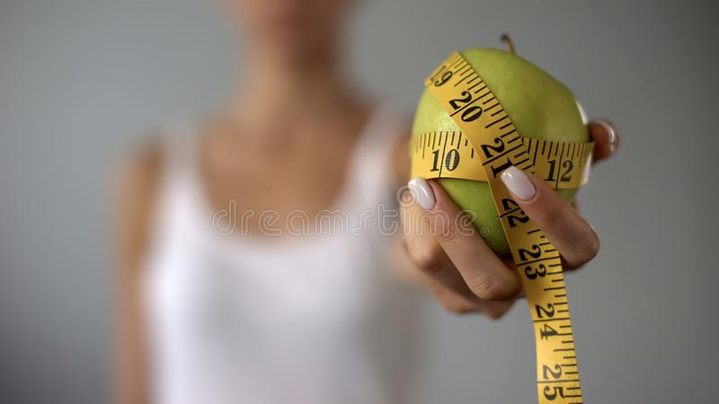 Girl holding apple tied with measuring tape, concept of healthy diet, vegetarian stock photography