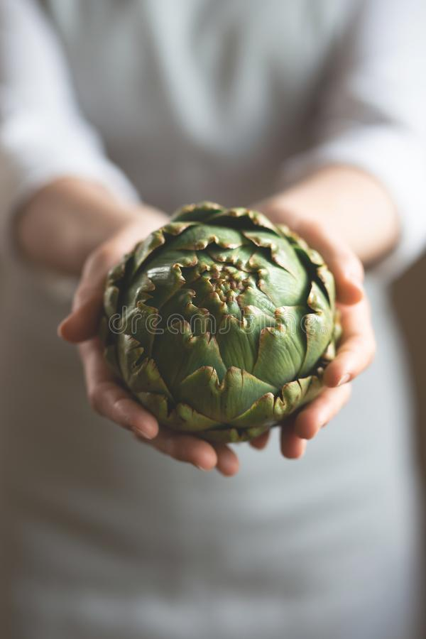 The girl is holding an artichoke with a blurred background, the concept of proper and dietary nutrition, dottex. Vertical picture royalty free stock images
