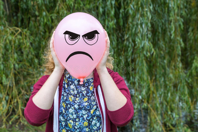 Girl holding balloon with angry face. Young woman holding balloon with angry expression in front of head outdoors with green natural background royalty free stock photography