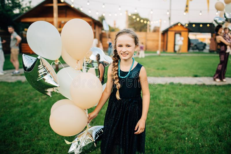 Girl holding balloons in the outdoor. Birthday party royalty free stock images