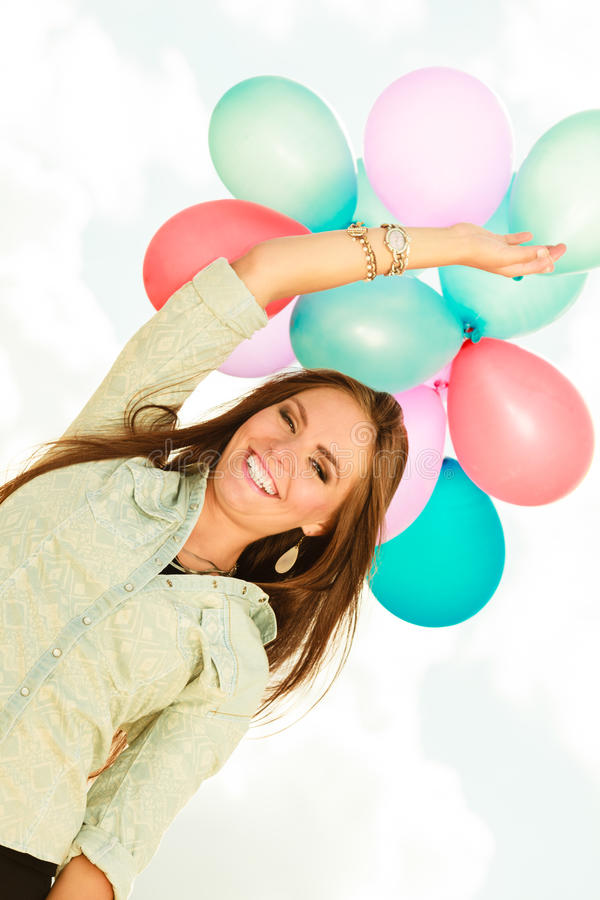 Girl holding balloons sky background. Holidays, celebration and lifestyle concept - attractive woman female model holding bunch of colorful balloons outside royalty free stock image