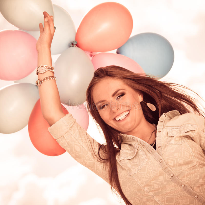 Girl holding balloons sky background. Holidays, celebration and lifestyle concept - attractive woman female model holding bunch of colorful balloons outside stock photos