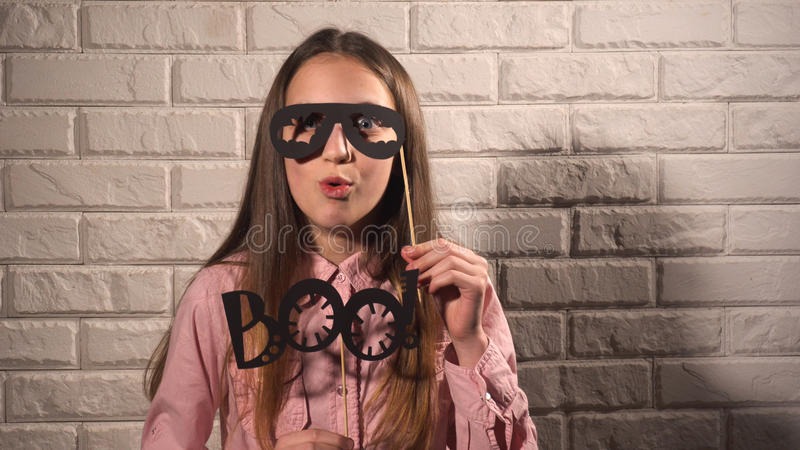 Girl holding a banner with black glasses. Nice girl in pink blouse holding banners with black glasses and phrase BOO on the background of white brick wall royalty free stock photography
