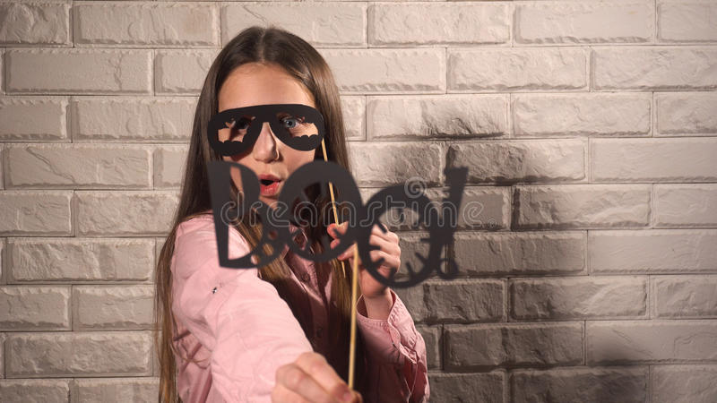 Girl holding a banner with black glasses. Pretty girl in pink blouse holding banners with black glasses and phrase BOO on the background of white brick wall stock images