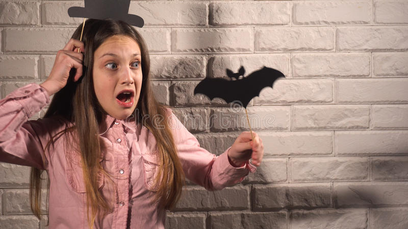Girl holding a banners with hat and bat. Funny girl in pink blouse holding banners with black hat and bat on the background of white brick wall royalty free stock photography