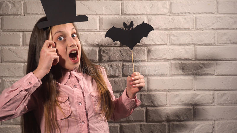 Girl holding a banners with hat and bat. Nice girl in pink blouse holding banners with black hat and bat on the background of white brick wall royalty free stock photo