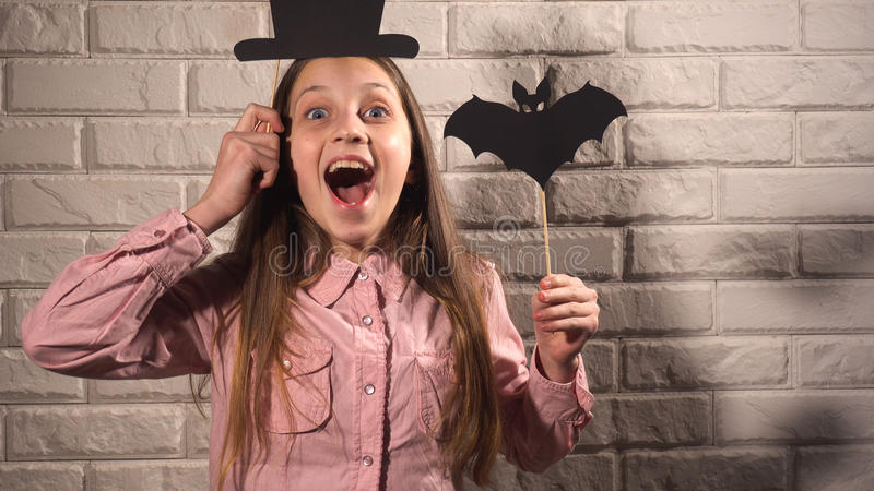 Girl holding a banners with hat and bat. Smiling girl in pink blouse holding banners with black hat and bat on the background of white brick wall royalty free stock images