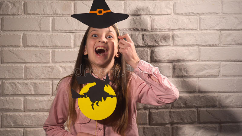 Girl holding a banners with hat and witch. Funny girl in pink blouse holding banners with black hat and witch on the background of white brick wall stock image