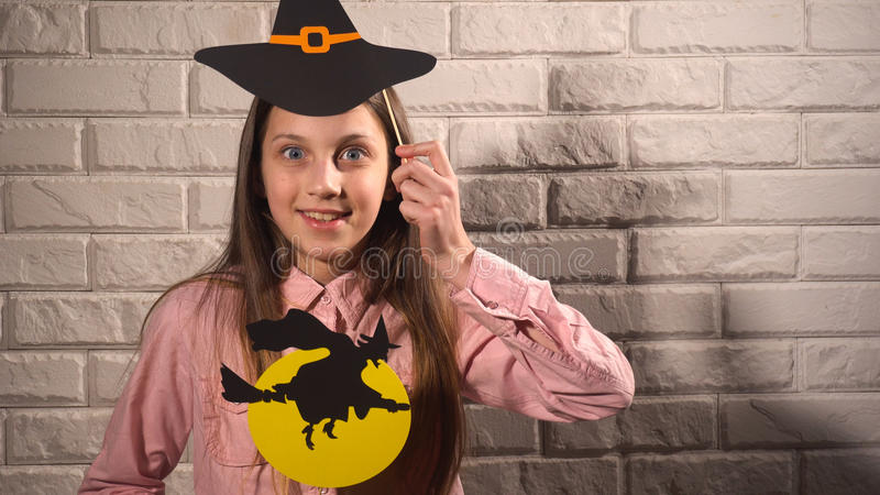 Girl holding a banners with hat and witch. Pretty girl in pink blouse holding banners with black hat and witch on the background of white brick wall royalty free stock images