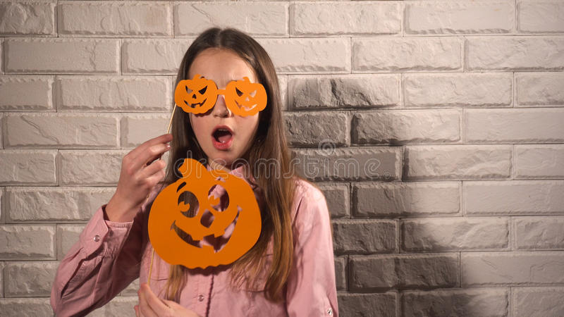 Girl holding a banners with pumpkins. Nice girl in pink blouse holding banners with orange pumpkins on the background of white brick wall royalty free stock images