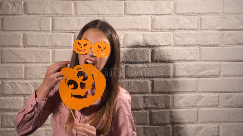Girl holding a banners with pumpkins. Pretty girl in pink blouse holding banners with orange pumpkins on the background of white brick wall royalty free stock photo