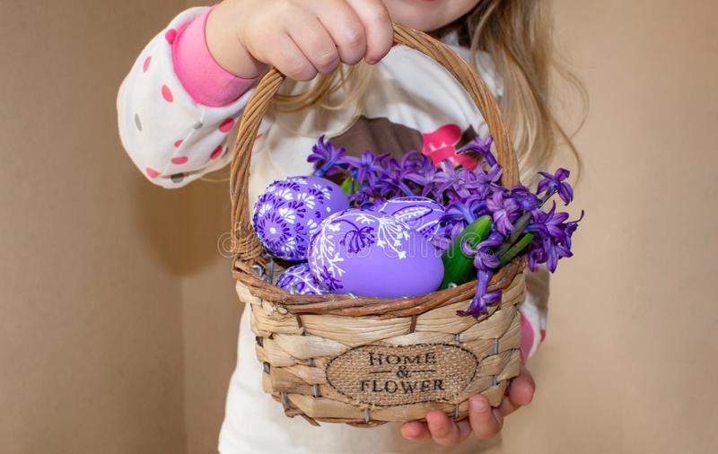 A girl holding a basket with painted eggs and flowers in lilac flowers, for Easter. stock photos