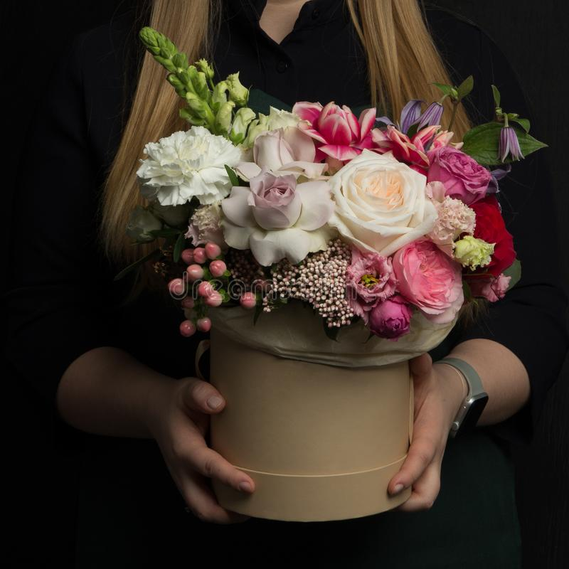 A girl is holding a beautiful bouquet of exclusive fresh flowers in a box. A great gift for women`s day, Valentine`s Day royalty free stock photos