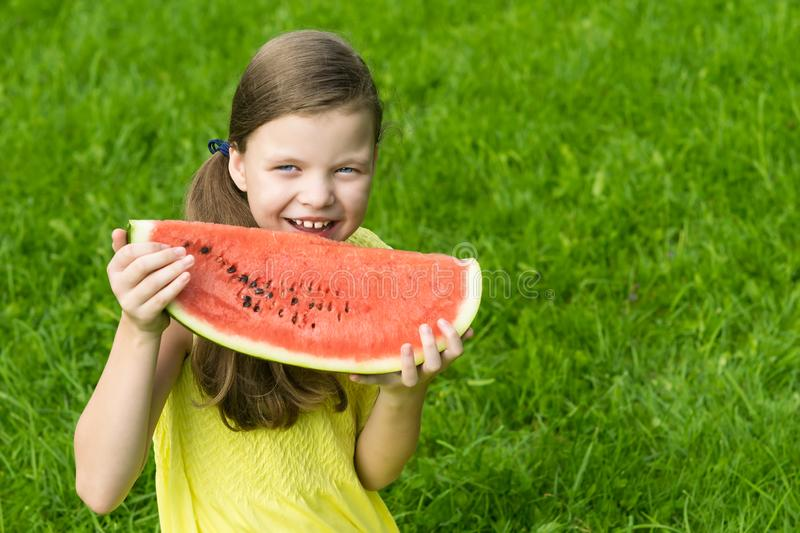 Girl holding a big red slice of watermelon in her hands and smiling stock photos