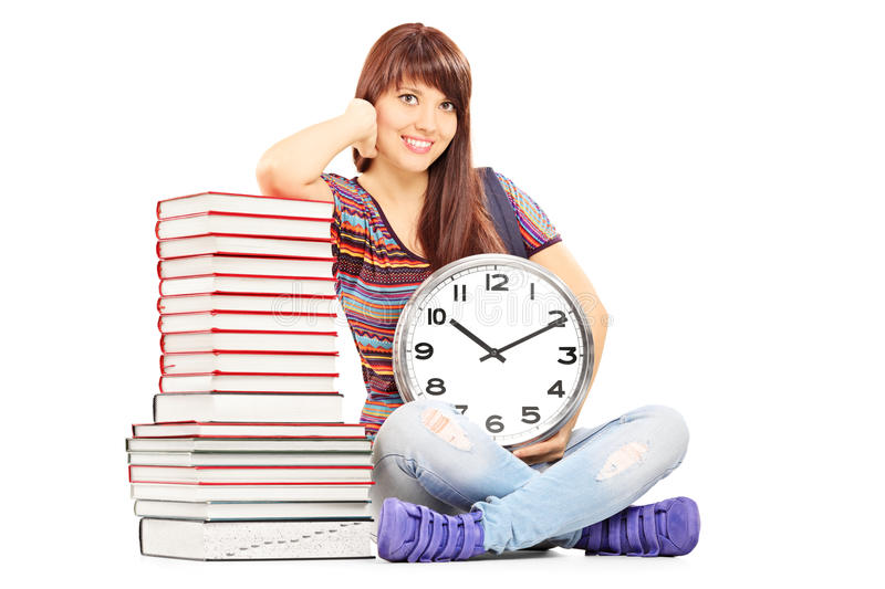 Girl holding big wall clock next to stack of books royalty free stock photo