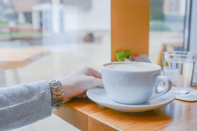 Girl holding big white cup of cafe latte in cafeteria on bright day. Close stock images