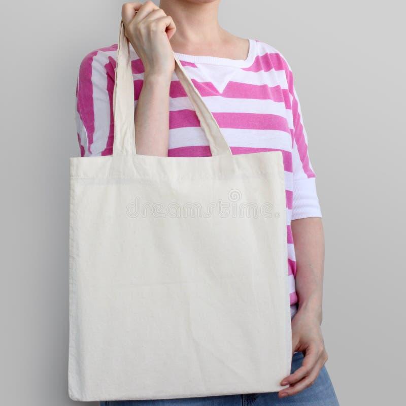 Girl is holding blank cotton eco bag, design mockup. stock photo