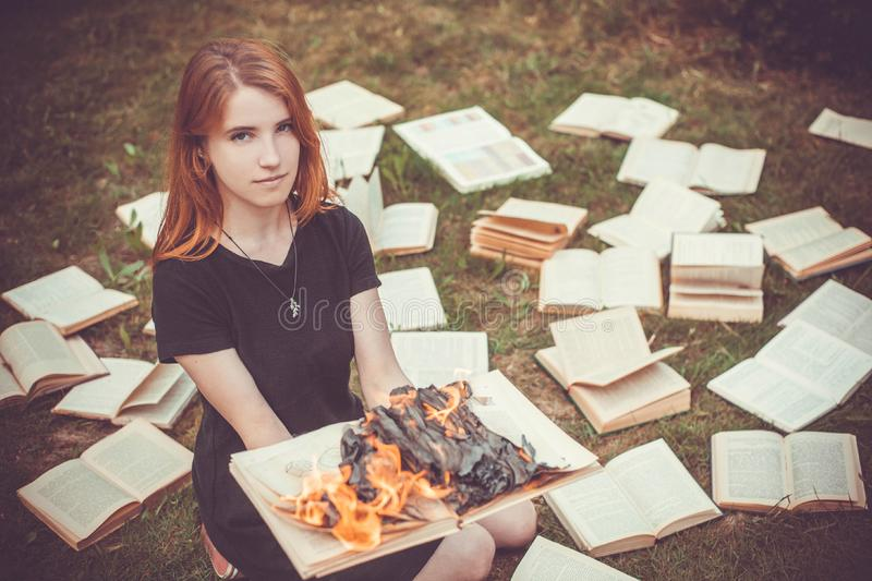 A girl holding a book burning in nature in summer garden royalty free stock image