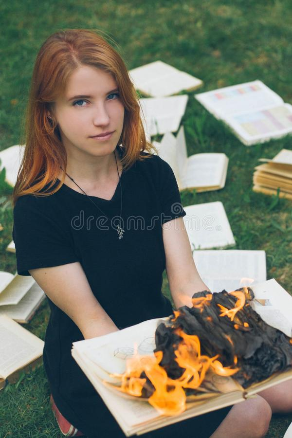 A girl holding a book burning in nature in summer garden royalty free stock photography
