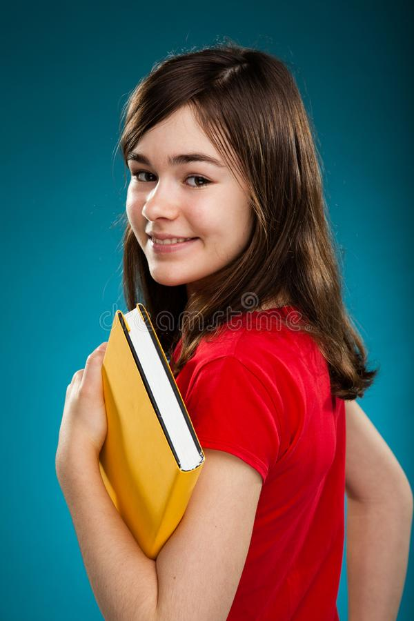 Girl holding book. On blue background stock photography