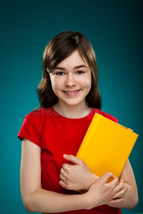 Girl holding book. On blue background stock photo
