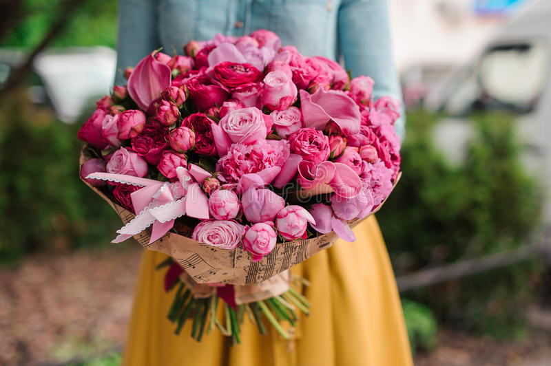 Girl holding a bouquet of pink flowers stock photography