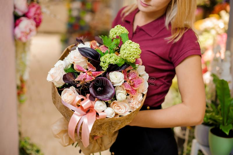 Girl holding a bouquet of roses, callas, orchid and hydrangea. In golden wrapping paper with a pink ribbon stock photography