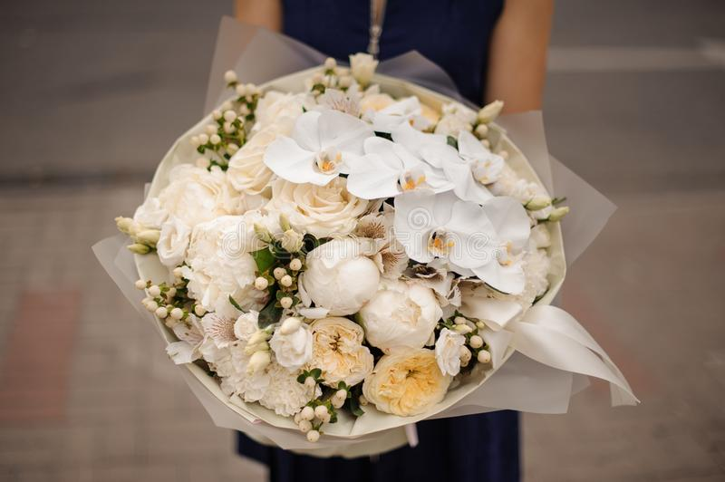 Girl holding bouquet of white orchids and champagne color peonies and roses. Girl in the blue dress holding in her hands a beautiful bouquet of white orchids and royalty free stock photo