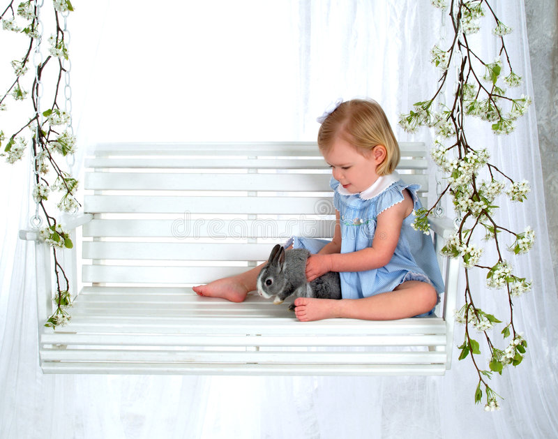 Girl Holding Bunny on Swing. Girl in blue sitting with bunny on swing in front of white background stock photos