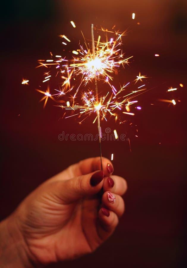 Girl holding a burning sparkler firework in her hand. Women holding a burning sparkler firework in her hand stock photography